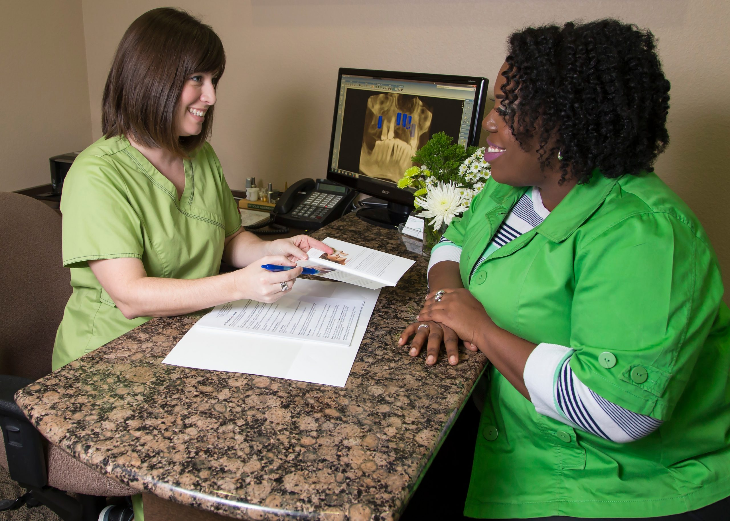 A patient and staff talking across a desk
