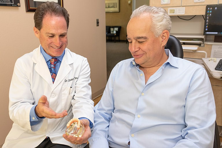 Dentist showing implant model to patient